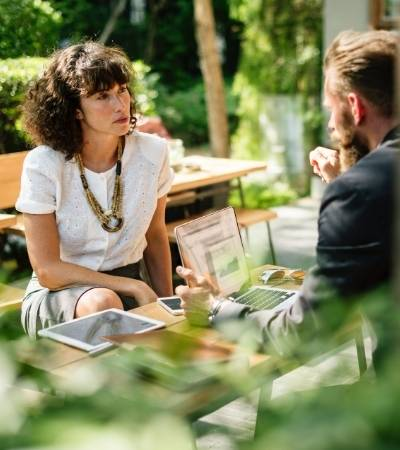 Image of a woman with dark curly hair sat at a table facing the camera and a man with his back to the camera. [Coaching and Mentoring For Sponsors]
